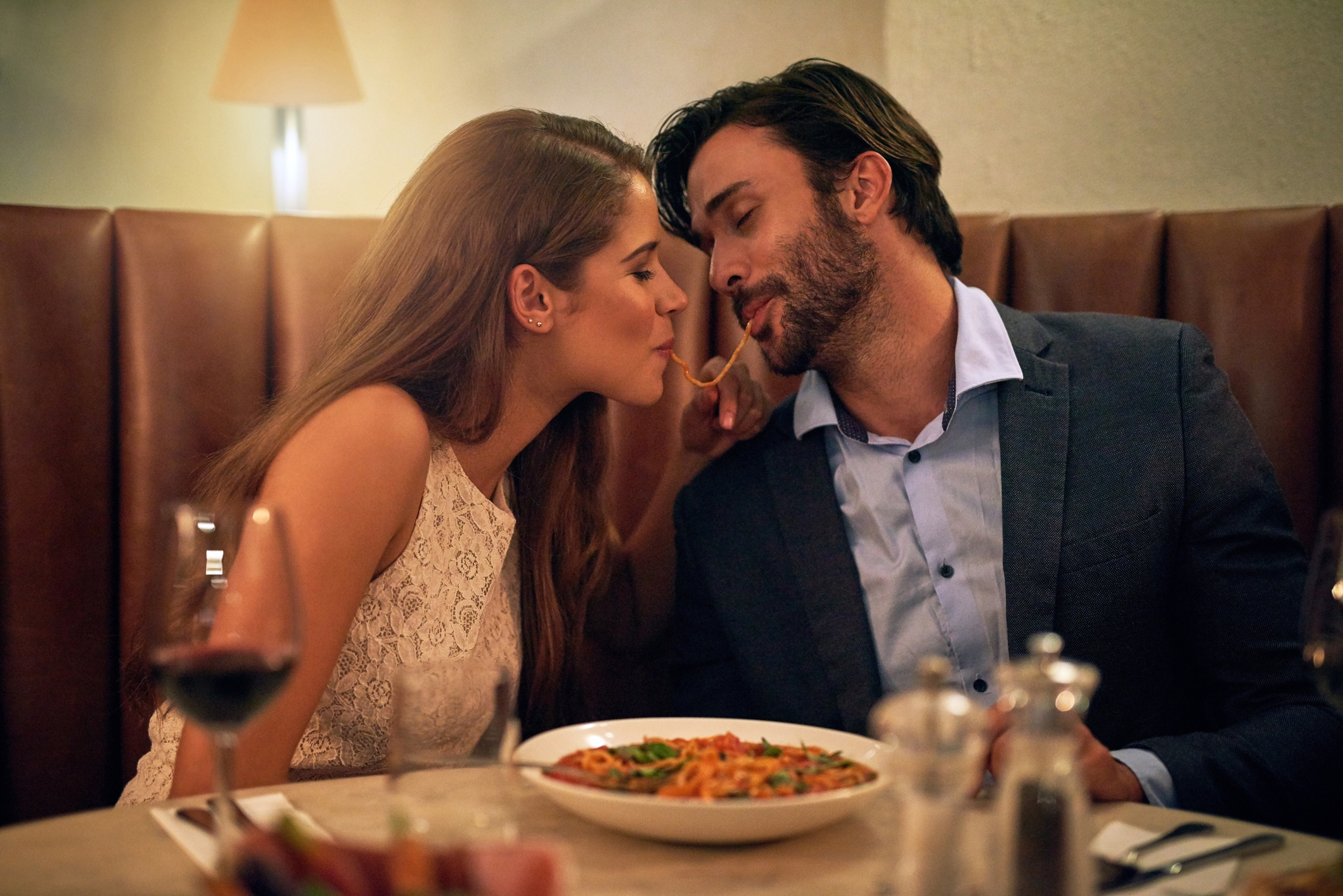 Couple share spaghetti on romantic date